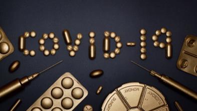 tabletki ułożone w napis covid-19 oraz strzykawki i leki