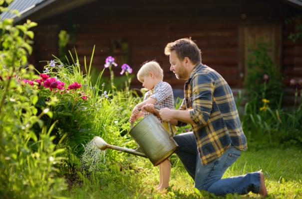 ojciec i syn podlewający razem kwiaty dużą konewką