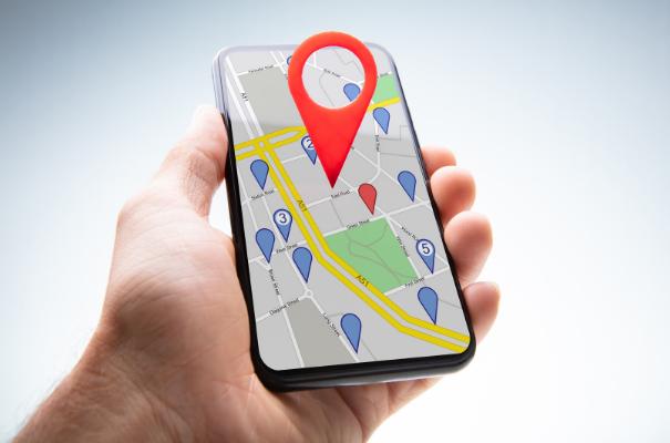 dłoń trzymająca smartfon z mapą, duża czerwona pinezka oznaczająca lokalizację