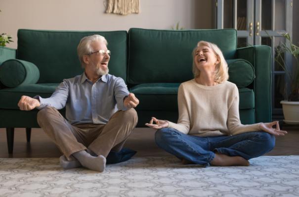 para uśmiechniętych seniorów na podłodze w salonie, pozycja z jogi