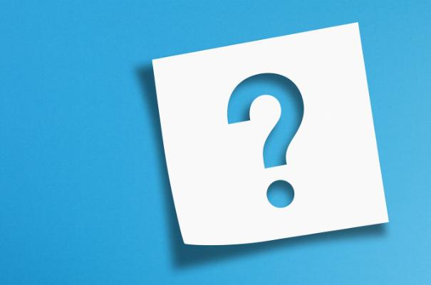 wycięty w białej kartce znak zapytania na niebieskim tle
