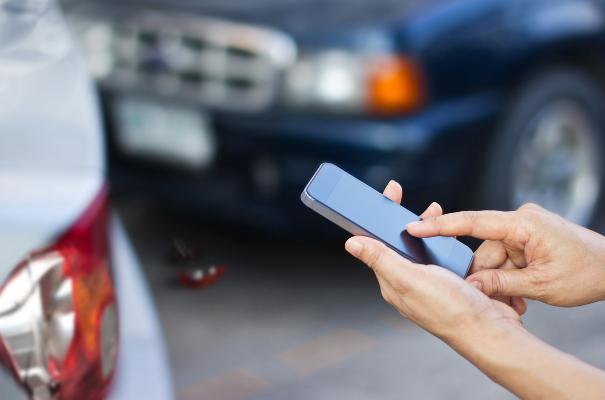 ręce trzymające smartfona, w le kolizja 2 aut