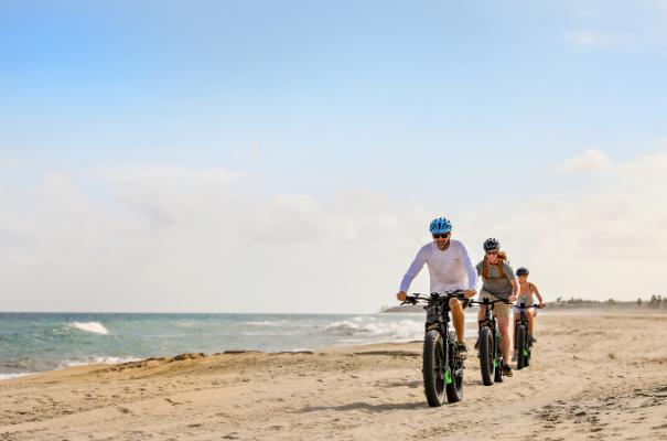 rodzina jadąca rowerami po plaży