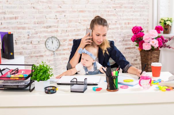 młoda kobieta rozmawiająca przez telefon z niemowlakiem na kolanach siedząca za biurkiem
