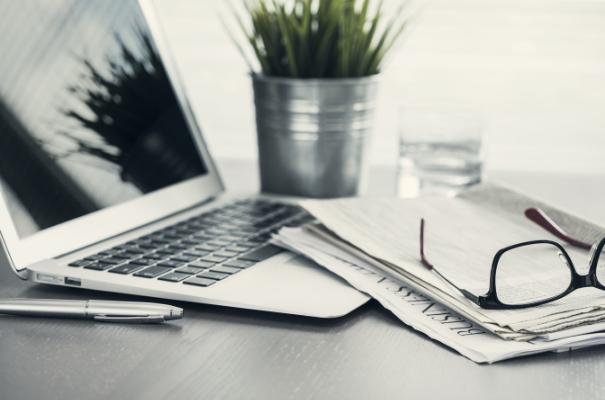 laptop, gazeta i okulary leżące na biurku