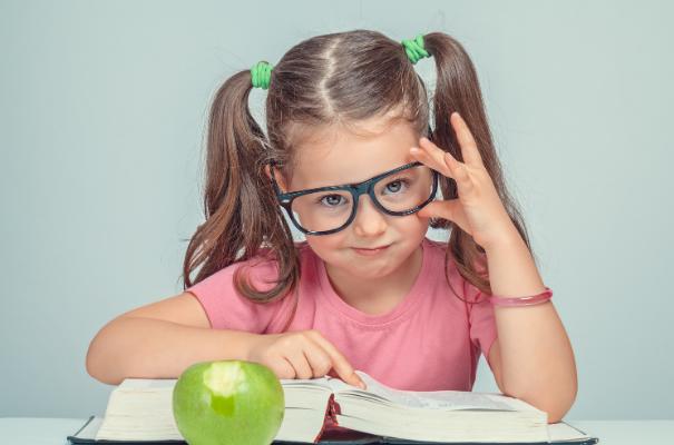 dziewczynka z kucykami patrząca znad okularów, siedząca nad ksiązką