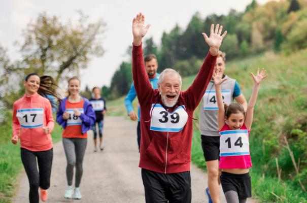 grupa biegaczy uśmiechnięty starszy pan finiszuje z rękoma w górze