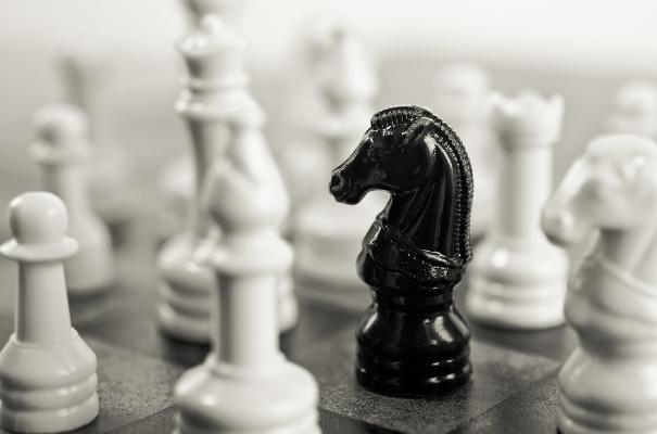 szachownica czarny goniec z towarzystwie białych figur