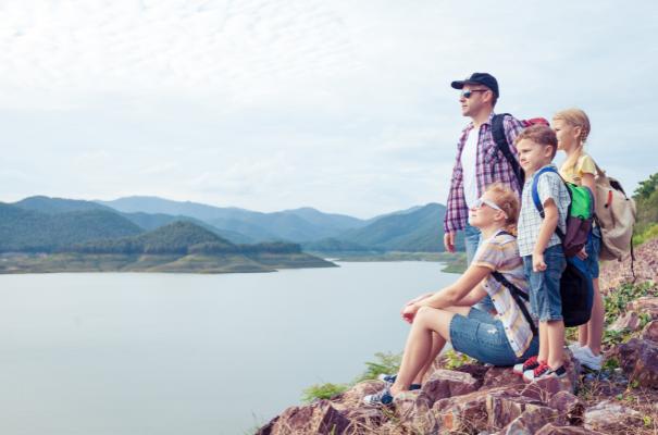 rodzina w wycieczce w górach, rodzice i dwoje dzieci podziwiają widok ze szczytu, w tle jezioro