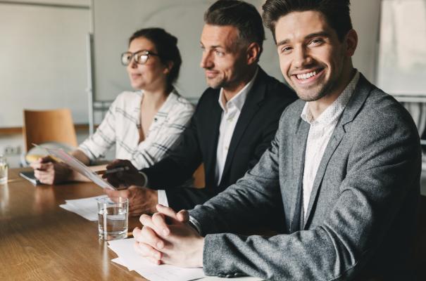 uśmiechnięty mężczyzna w garniturze, siedzący w biurze z dwoma współpracownikami
