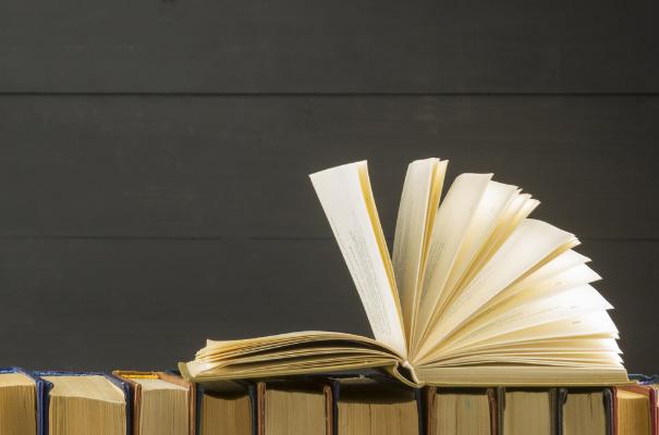 otwarta książka leżąca na rzędzie książek